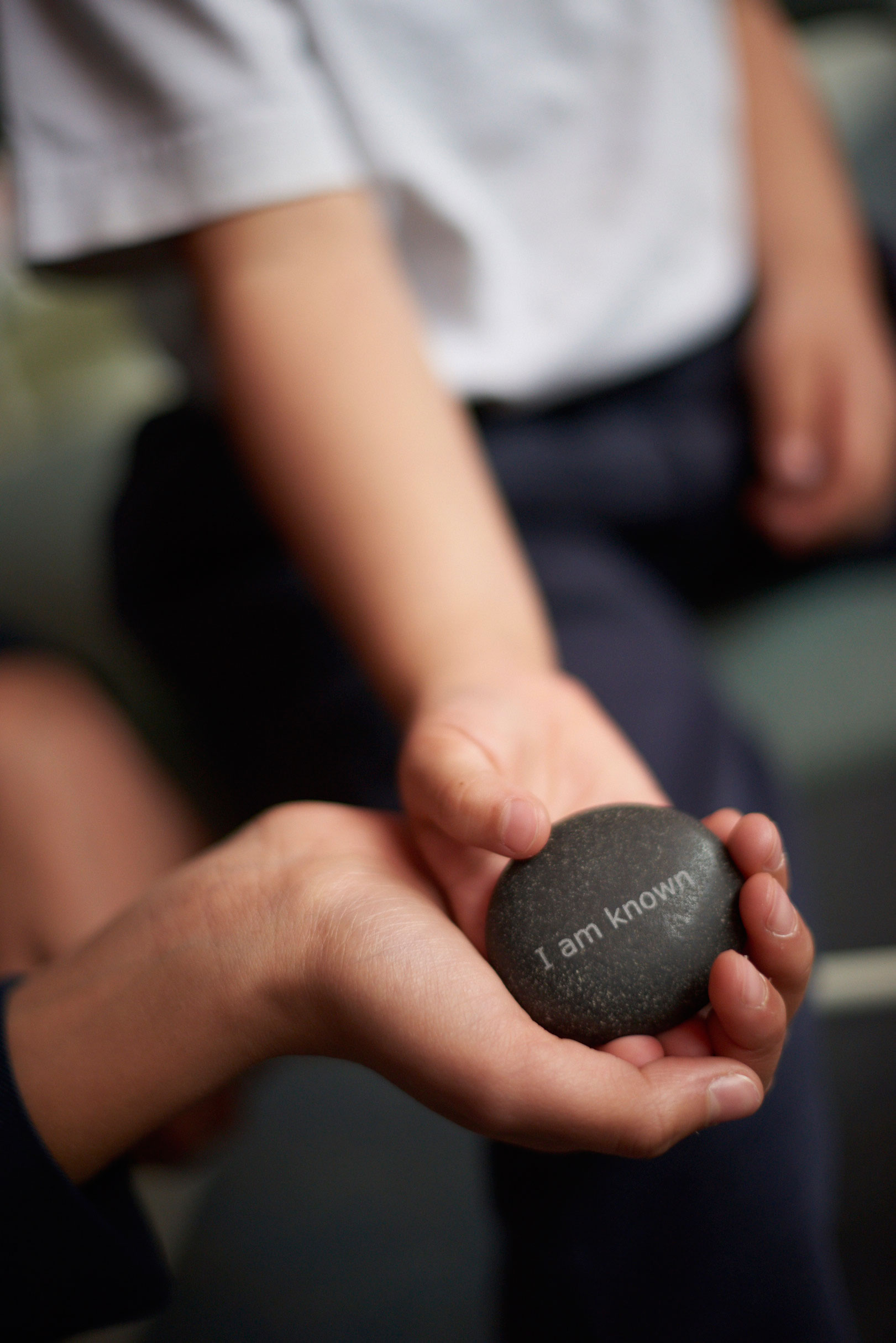 Student holding the I am known stone